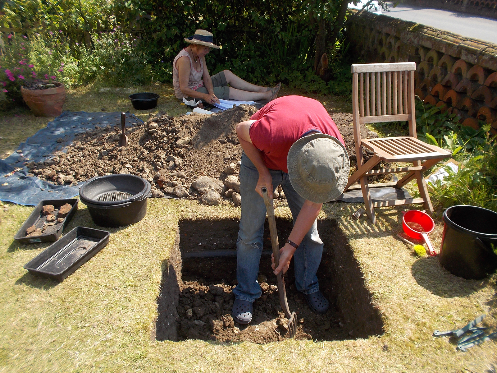 Volunteers working on a test pit in their garden at Hoxne