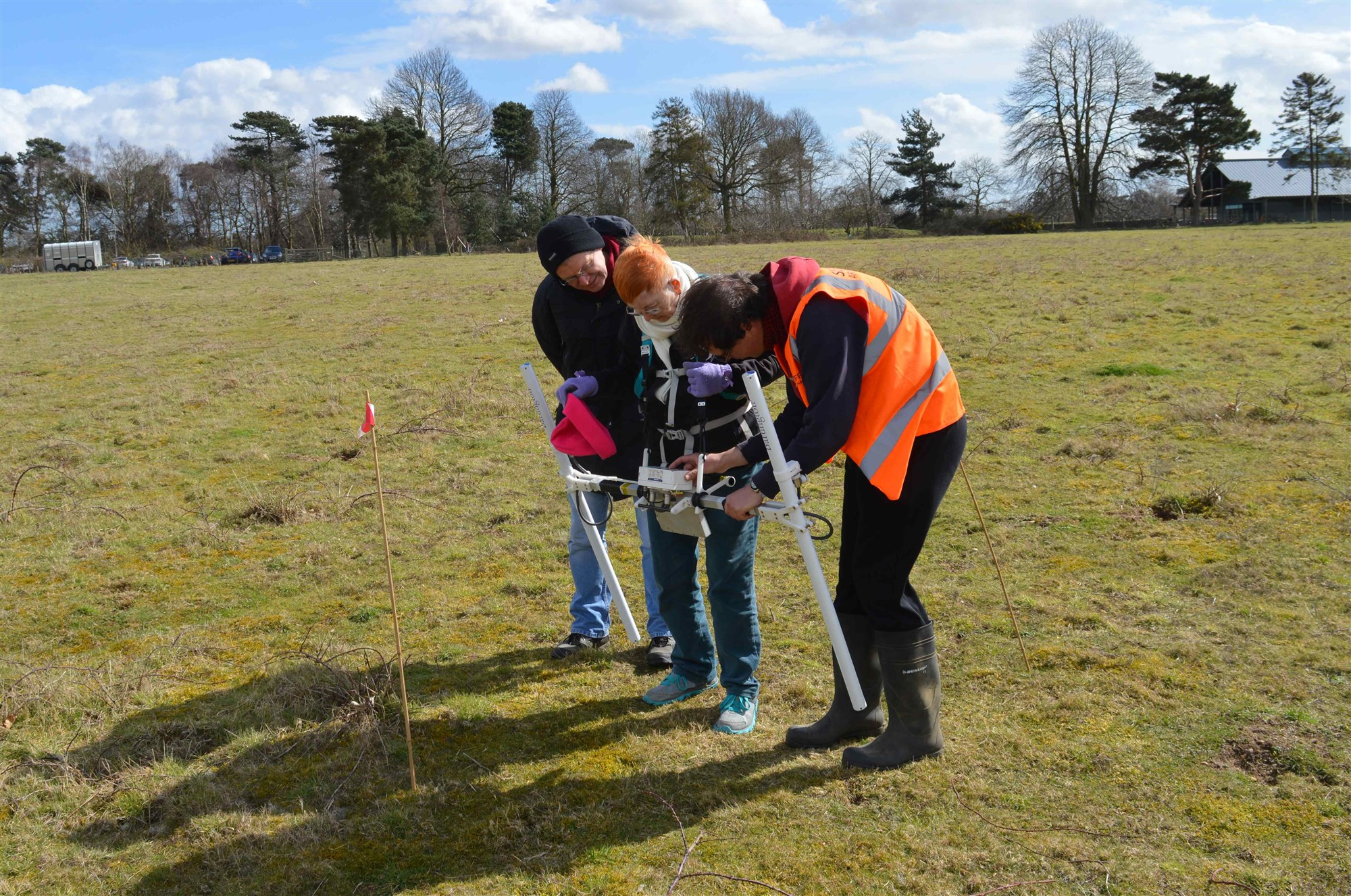 Showing volunteers how to use the magnetometer at Sutton Hoo