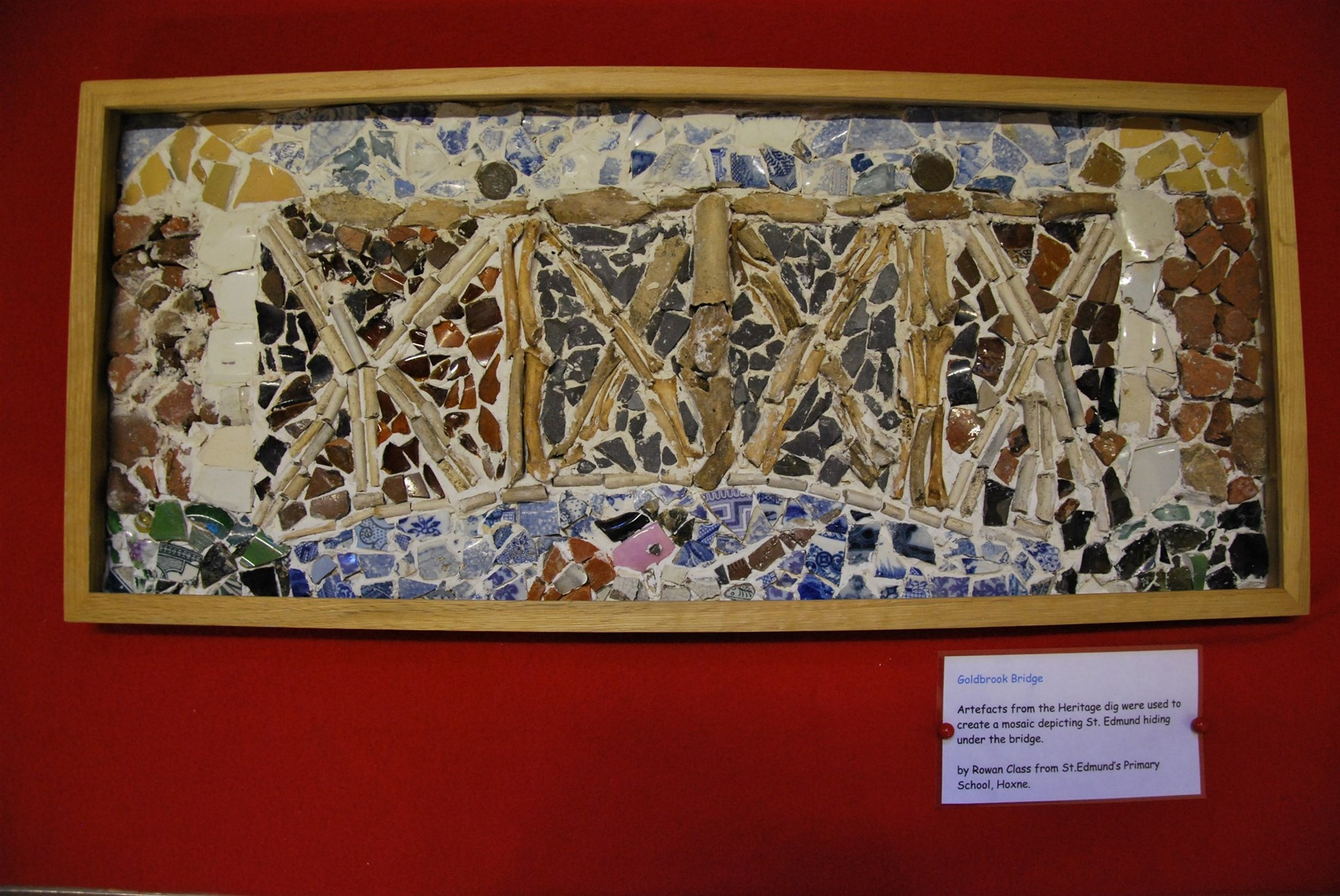 Mosaic depicting the legend of St Edmund hiding under Goldbrook Bridge, Hoxne, created by Hoxne schoolchildren using finds from their test pits