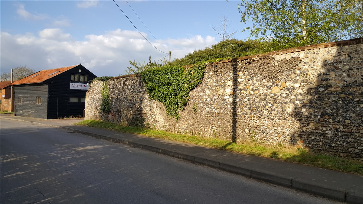 Surviving length of medieval flint wall incorporated into the Grade II listed curtilage wall on the road frontage.